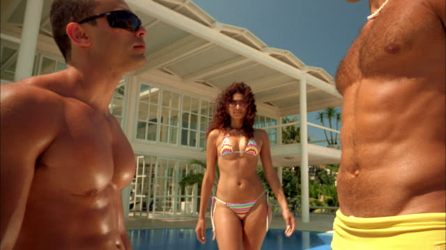 medium shot woman in bikini posing seriously between two barechested men at swimming pool - chest hair stock videos and b-roll footage