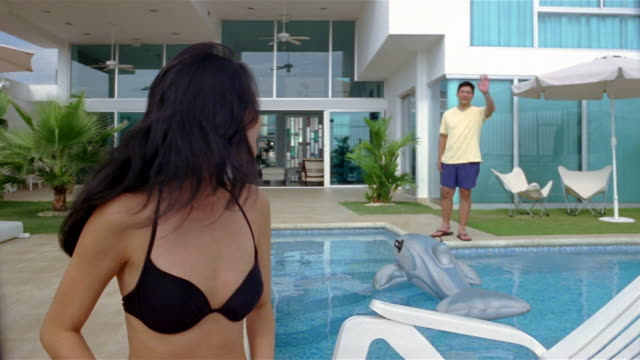 medium shot woman in bikini sitting near pool / turning around and waving at man standing on other side of pool - flip flop stock videos and b-roll footage