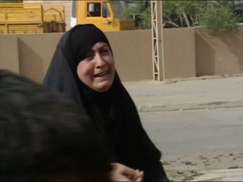 stockvideo's en b-roll-footage met medium shot woman in black hijab weeping on street being consoled by journalist / baghdad, iraq - 2003