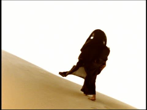 Medium shot woman in black veil walking on desert dune and leaving footprints / Egypt