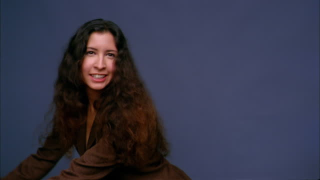 medium shot woman in blazer w/long hair smiling and dancing against blue background - coloured background stock videos and b-roll footage