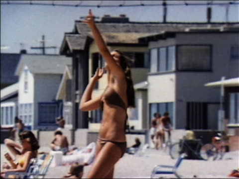 vídeos de stock, filmes e b-roll de 1970 medium shot woman in brown bikini serving volleyball on beach / audio narrator - biquíni