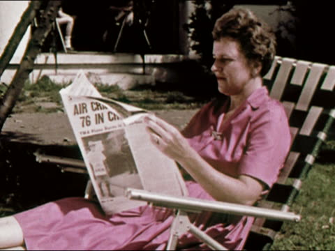 1964 Medium shot woman in chaise lounge reading New York Newsday / Long Island, New York / AUDIO