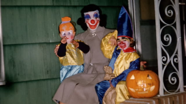 stockvideo's en b-roll-footage met 1955 medium shot woman in clown mask and two children in halloween costumes waving at cam - archival