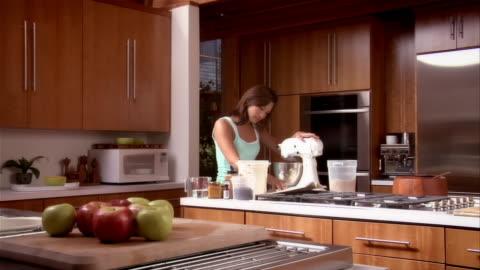 medium shot woman in kitchen reading recipe and using mixer - waschbecken stock-videos und b-roll-filmmaterial