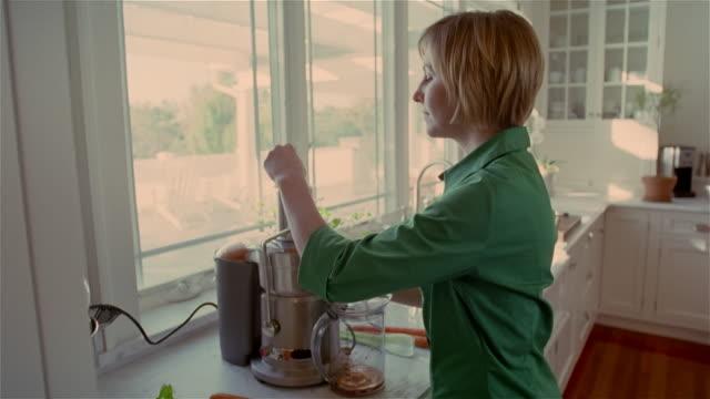 vídeos de stock, filmes e b-roll de medium shot woman in kitchen using juicer/ solebury, pennsylvania - aipo
