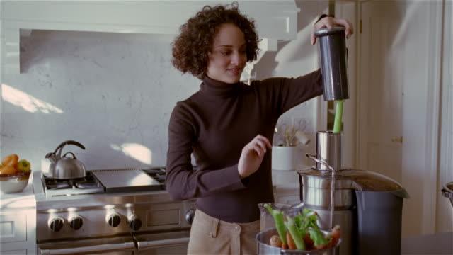 vídeos de stock e filmes b-roll de medium shot woman in kitchen using juicer/ solebury, pennsylvania - gola alta