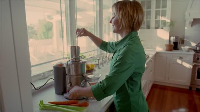 medium shot woman in kitchen using juicer/ solebury, pennsylvania - juice extractor stock videos & royalty-free footage