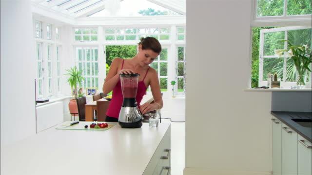 Medium shot woman in modern kitchen making smoothie in blender/ London