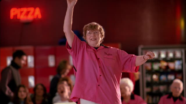 vídeos de stock, filmes e b-roll de medium shot  woman in 'pink ladies' jersey bowling and cheering w/teammates - cancha de jogo de boliche