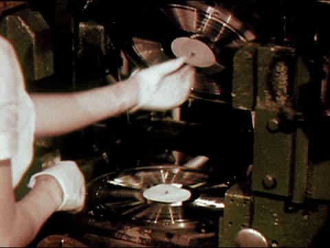 stockvideo's en b-roll-footage met 1956 medium shot woman in record factory affixing labels to press, adding blob of pvc, and closing press/ audio - vinylplaat