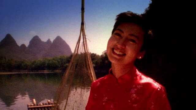 vidéos et rushes de medium shot woman in red dress smiling on pier with rock formations in background / li river, china - robe rouge