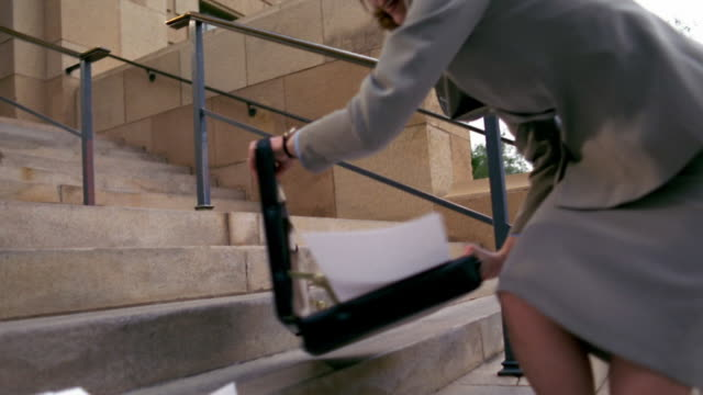 medium shot woman in suit kneeling on stairs picking up scattered papers - briefcase stock videos and b-roll footage