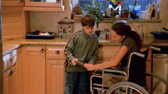 medium shot woman in wheelchair working in kitchen / son running in with homework / mother helping son - thank you stock videos and b-roll footage