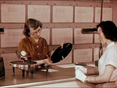 1956 medium shot woman inspects and tests phonograph record at record plant as other woman watches/ audio - schallplatte stock-videos und b-roll-filmmaterial