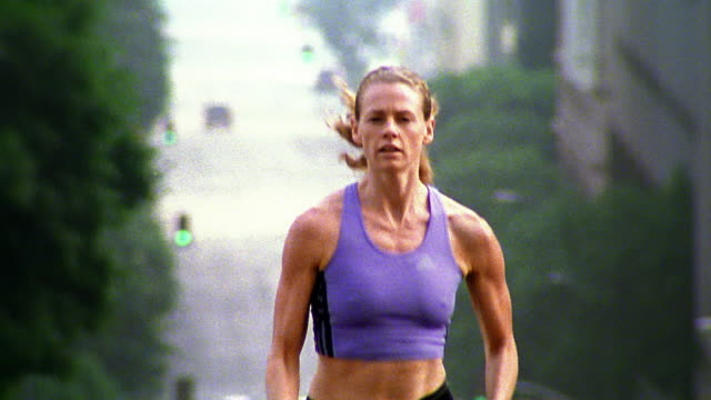medium shot woman jogging on city street / los angeles - sportbehå bildbanksvideor och videomaterial från bakom kulisserna