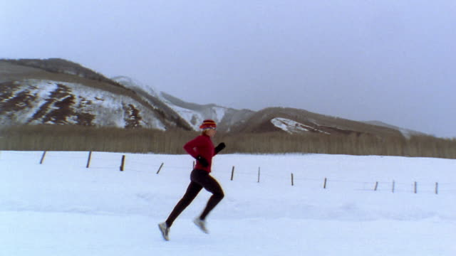 medium shot woman jogging on snowy road w/mountains and trees in background / vail, colorado, usa - colorado stock videos & royalty-free footage