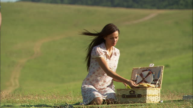 medium shot woman kneeling on grass, taking food out of picnic basket/ man walking in, kneeling, hugging and kissing woman/ umbria - picnic basket stock videos and b-roll footage