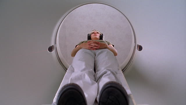 Medium shot woman laying on platform and emerging from CAT scan machine