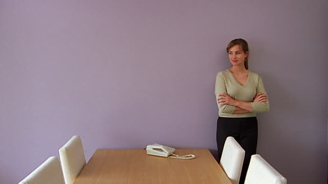 medium shot woman leaning against wall in empty conference room - v neck stock videos & royalty-free footage
