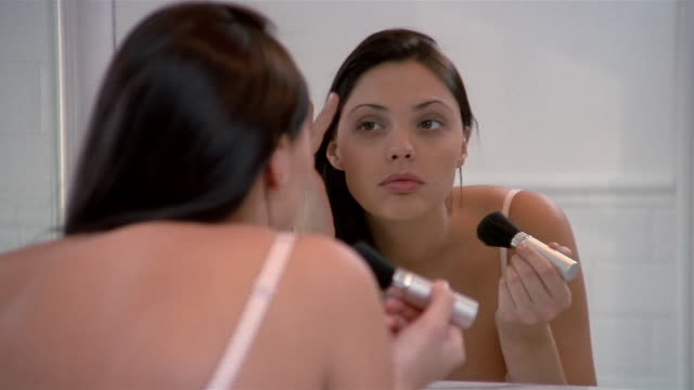 medium shot woman leaning into mirror / applying blush / fixing hair - フェイスブラシ点の映像素材/bロール
