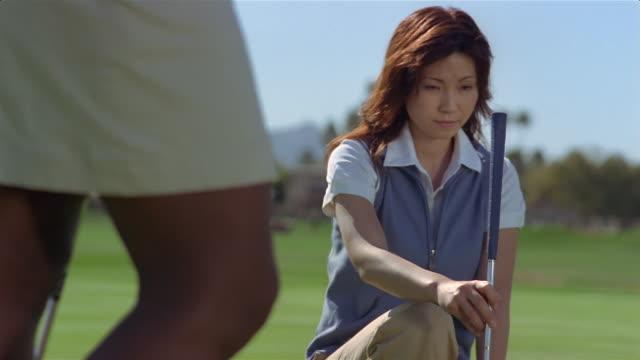 Medium shot woman lining up golf putt