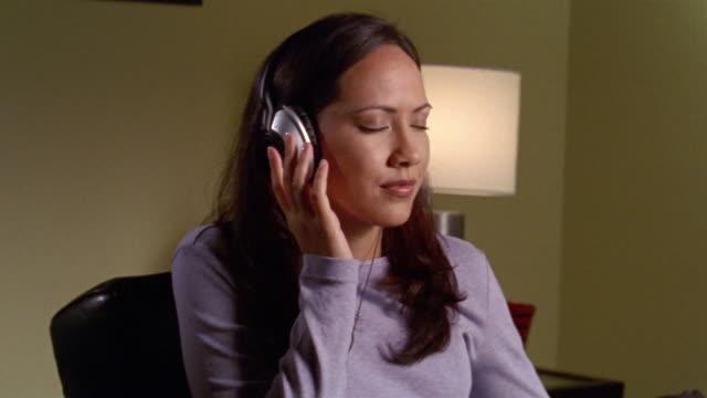 vidéos et rushes de medium shot woman listening to music with headphones - seulement des jeunes femmes