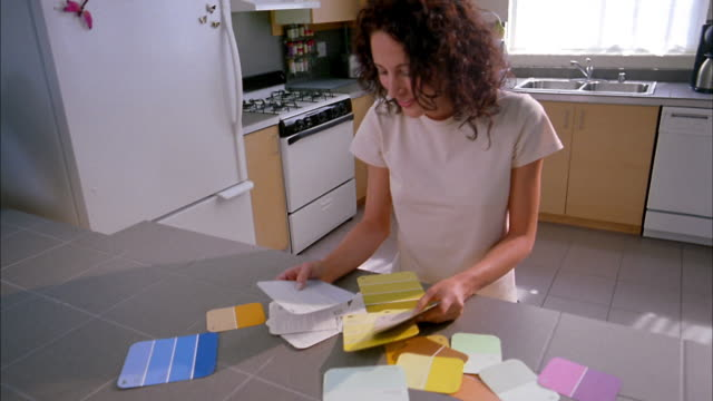 Medium shot woman looking at color paint samples on kitchen counter
