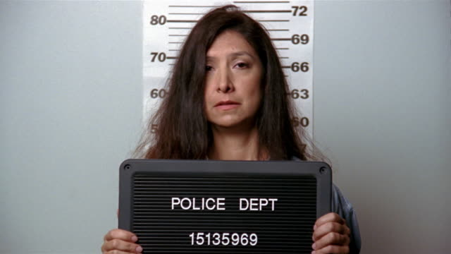 medium shot woman looking worried and looking around while posing for mug shot - mug shot stock videos & royalty-free footage