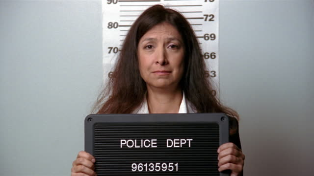 medium shot woman looking worried while posing for mug shot - mug shot stock videos & royalty-free footage