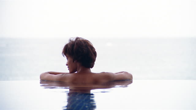 vidéos et rushes de medium shot woman lounging in pool facing away from cam - rebord de piscine