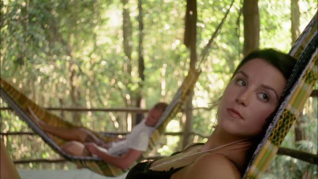 medium shot woman lying in hammock listening to headphones / man lying in hammock in the background / the amazon, brazil - hammock stock videos & royalty-free footage