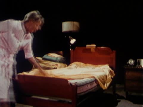 1972 medium shot woman making bed / man in bathrobe shaving and watching her /  audio - housework stock videos & royalty-free footage