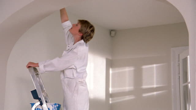 medium shot woman on ladder painting wall / stopping, wiping forehand, climbing down and leaving w/paint bucket - forehand stock videos & royalty-free footage