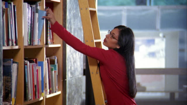 vidéos et rushes de medium shot woman on ladder taking book from library shelf and smiling at cam - échelle