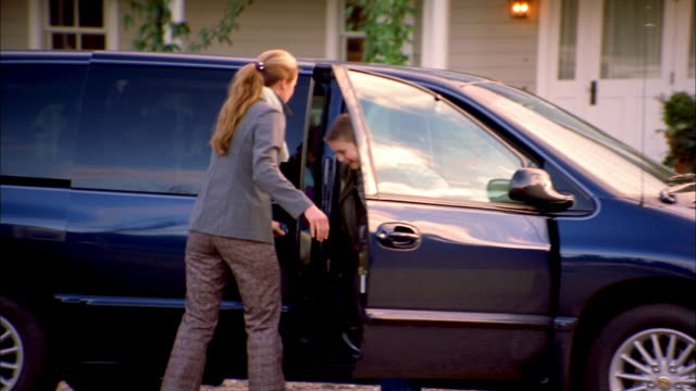 Medium shot woman opening door of van parked in driveway / group of children getting out and walking to house