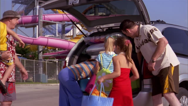 Medium shot woman opening trunk of minivan / family unloading inflatable water toys