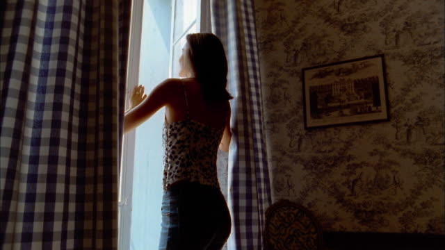 medium shot woman opening window and enjoying view - curtain stock videos & royalty-free footage