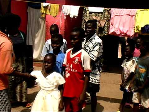 Medium shot woman organizing children for family portrait/ Ghana