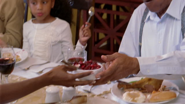Medium shot woman passing cranberry sauce at holiday dinner / grandfather putting sauce on his plate