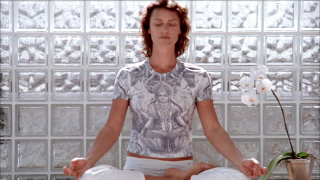 medium shot woman performing yoga and sitting w/eyes closed in 'lotus' position - lotus position stock videos & royalty-free footage