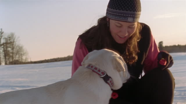 Medium shot Woman petting dog in snowy field / Cumberland County, Maine, USA