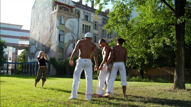 Medium shot. Woman photographing group of male Capoeira dancers.