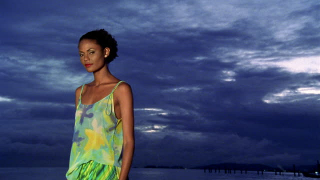 vidéos et rushes de medium shot woman posing near water and looking at cam with dark sky in background - kelly mason videos