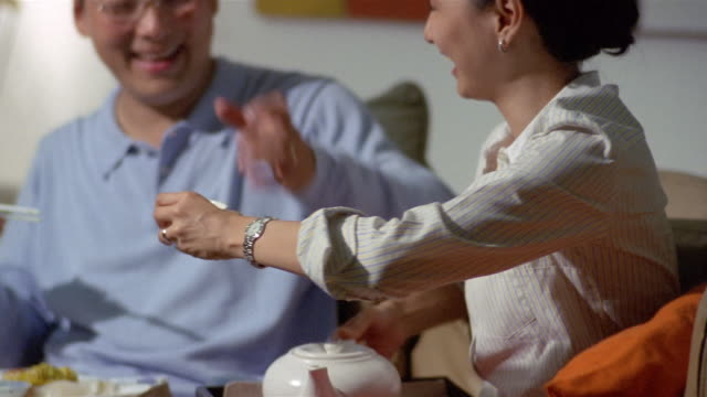 medium shot woman pouring and serving tea to husband at meal / couple making toast / husband feeding wife dim sum with chopsticks - beccuccio video stock e b–roll