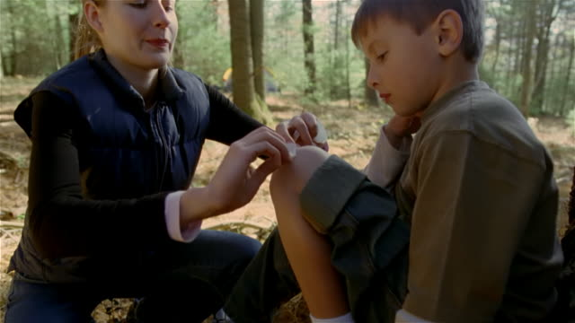 Medium shot woman putting bandage on boy's knee / kissing it