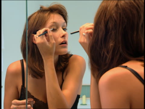 vídeos y material grabado en eventos de stock de medium shot woman putting on eye makeup in bathroom mirror - maquillaje para ojos