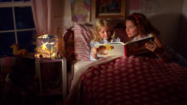 medium shot woman reading children's book to young blonde girl in bed - storytelling stock videos and b-roll footage