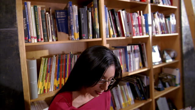 medium shot woman reading in library removing glasses and smiling at cam - reading glasses stock videos & royalty-free footage