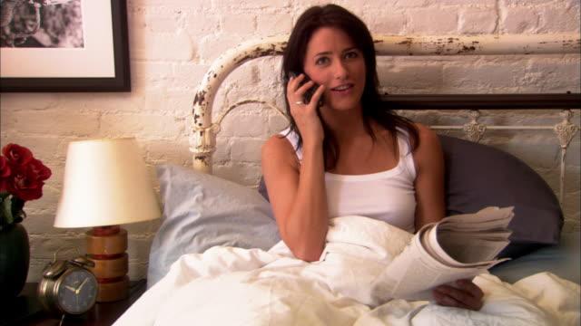 stockvideo's en b-roll-footage met medium shot woman reading newspaper in bed, then answering telephone - draadloze telefoon